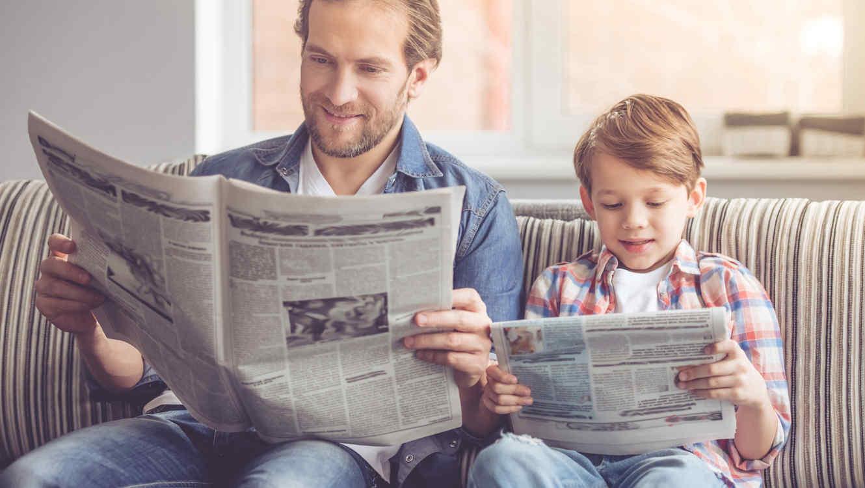 padre-e-hijo-leyendo-periodicos-en-sofa
